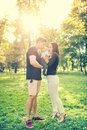 Happy family in park, mother and father holding and kissing a few months old son, kid. Infant portrait and happy family concept Royalty Free Stock Photo
