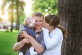 Happy family in the park in spring sunny day kissing of daddy Royalty Free Stock Photo