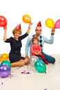 Happy family partying with balloons and confetti Stock Photos