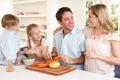 Happy family peeling vegetables in kitchen