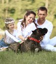 Happy family with pet dog at picnic in a Sunny summer day. pregn Royalty Free Stock Photo