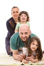 Happy family piled on top of little girl home having fun isolated white background Stock Photos