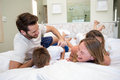Happy family playing on the bed Royalty Free Stock Photo