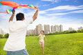 Happy family playing colorful kite in the city park enjoy time Stock Images
