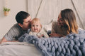 Happy family playing at home on the bed. Lifestyle capture of mother, father and baby Royalty Free Stock Photo