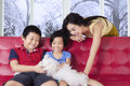 Happy family playing puppy on the sofa Royalty Free Stock Photo