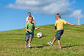 Happy family is playing soccer in summer Royalty Free Stock Image