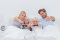 Happy family playing video games in bed Royalty Free Stock Photo