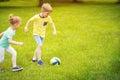 Happy family plays football in sunny park