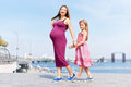 Happy family, pregnant mother and her daughter little girl child walking and hugging on the embankment in the summer day Royalty Free Stock Photo