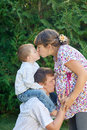 Happy family. Pregnant mother with her husband and son in the park. Mum kisses the son and dad kissing mums belly Royalty Free Stock Photo