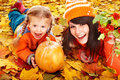 Happy family with pumpkin on autumn leaves outdoor Stock Image