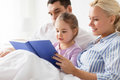 Happy family reading book in bed at home Royalty Free Stock Photo