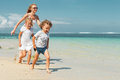 Happy family running on the beach Royalty Free Stock Photo