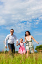 Happy family running on meadow in summer Stock Photos