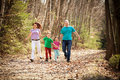 Happy family running in the woods holding hands and having a fun time along a path forest Royalty Free Stock Photography