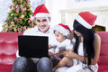 Happy family in santa hat using a laptop wearing computer at home Stock Photos