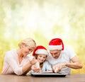 Happy family in santa helper hats making cookies