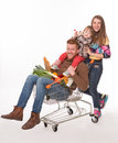 Happy family with a shopping cart in supermarket Royalty Free Stock Photo