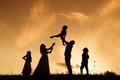 Happy family silhouettes of parents having fun with their children Stock Photo
