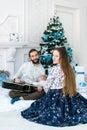 Happy family sing Christmas Carols under a fir-tree.