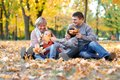 Happy family sit in autumn city park on fallen leaves. Children and parents posing, smiling, playing and having fun. Bright yellow Royalty Free Stock Photo