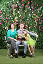Happy family sit on bench with bunch of flowers three in garden near verdant hedge Stock Image