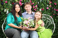 Happy family sit on bench of three hold flowers and look at camera in garden near verdant hedge Royalty Free Stock Photography