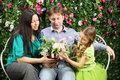 Happy family sit on white bench and hold flowers of three in garden near verdant hedge Stock Photography