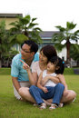 Happy family sits on grass field Stock Images