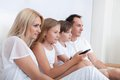 A Happy Family Sitting In Bed Watching Tv Stock Photography