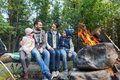 Happy family sitting on bench at camp fire Royalty Free Stock Photo