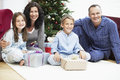 Happy family sitting in front of christmas tree portrait parents and children with presents Stock Photography