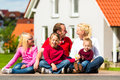 Happy family sitting in front of home Royalty Free Stock Image