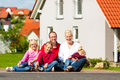 Happy family sitting in front of home young the sun their new and laughing Royalty Free Stock Photos