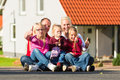 Happy family sitting in front of home young the sun their new and laughing Royalty Free Stock Images