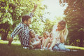 Happy family sitting on grass in the meadow together and enjoyin Royalty Free Stock Photo