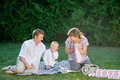 Happy family sitting on the grass in a park with letters love Royalty Free Stock Photo