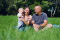 Happy family sitting in a green grass at sunny day Stock Image