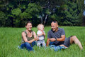 Happy family sitting in a green grass at sunny day Royalty Free Stock Image