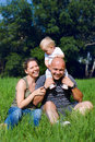 Happy family sitting in a green grass at sunny day Stock Photo