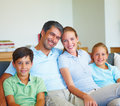 Happy family sitting in the living room smiling Stock Photo