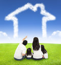 Happy family sitting on a meadow with house of clouds Royalty Free Stock Photo