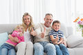 Happy family sitting on sofa giving thumbs up Royalty Free Stock Photo