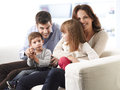 Happy family sitting on sofa in living room Royalty Free Stock Image
