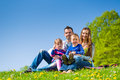 Happy family sitting in summer meadow with daughter and son a Royalty Free Stock Photography