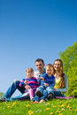 Happy family sitting in summer meadow with daughter and son a Royalty Free Stock Images