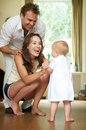 Happy family smiling as baby takes first steps portrait of a Royalty Free Stock Image