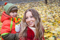 Happy family smiling and holding autumn leaves in park Stock Images