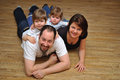 Happy family smiling at home on wooden floor